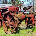 Rusted Red Antique Tractor With Metal Wheels
