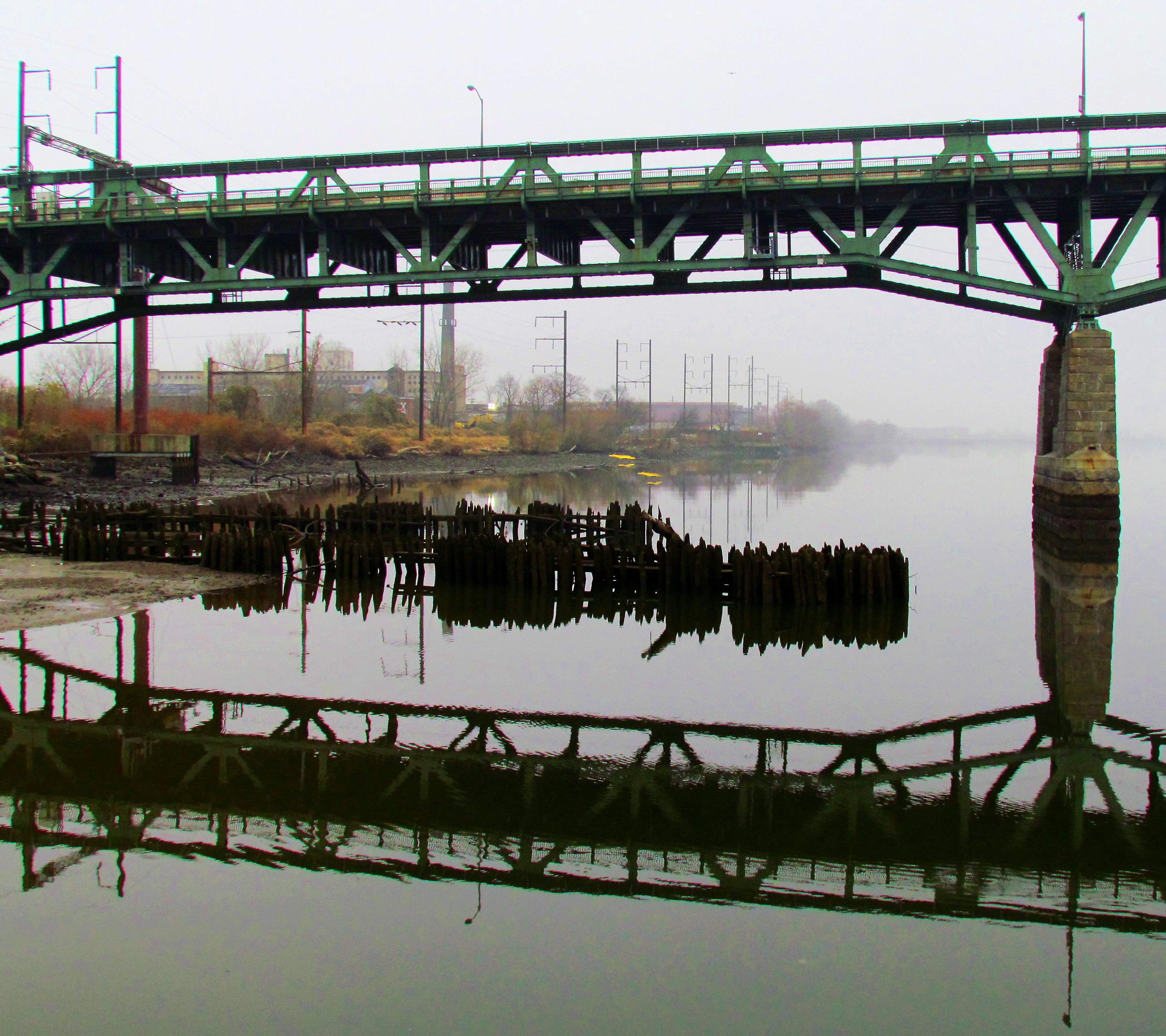 Reflections Of Steel Bridge Span, Pillar, & River Jetty